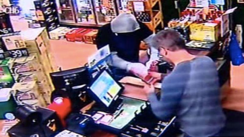 The cashier hands over money after having a gun pointed at him. Photo: CCTV