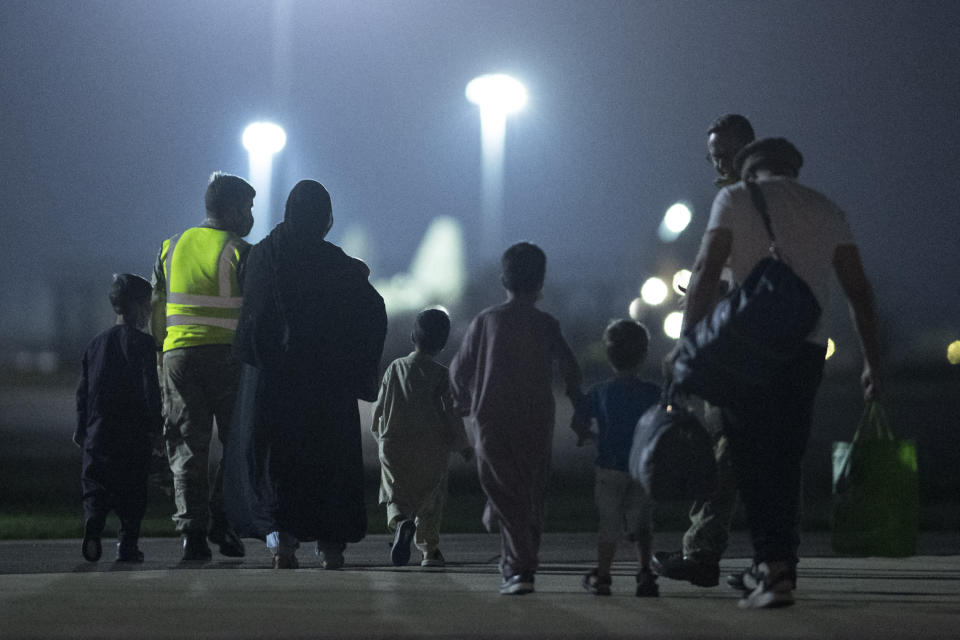 TOPSHOT - Passengers evacuated from Afghanistan disembark from a British Royal Air Force (RAF) Airbus KC2 Voyager aircraft, after landing at RAF Brize Norton station in southern England on August 24, 2021. - Britain said on August 23 it would urge the United States to extend an end-of-the-month deadline for evacuations from Afghanistan, while the Taliban warned any delay would lead to