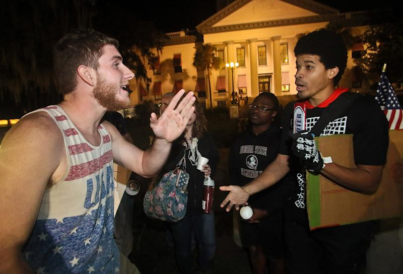 Donald Trump supporter Ben Kilgore, (L), discusses the president-elect's merits with protester Brandon Nathaniel Collier, who is demonstrates against Trump's election as President of the United States, in Tallahassee, Fla., on Nov. 16, 2016. REUTERS/Phil Sears/Reuters)