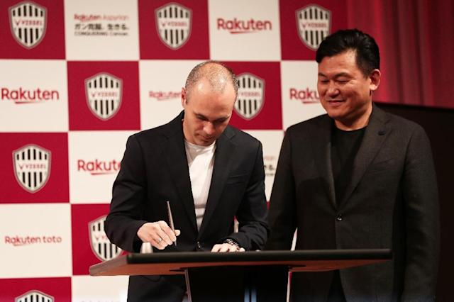Spain legend Andres Iniesta signs his Vissel Kobe contract watched by club owner Hiroshi Mikitani (AFP Photo/Behrouz MEHRI)