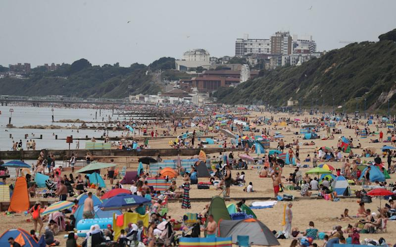 People enjoy the hot weather at Boscombe beach in Dorset - Andrew Matthews/PA