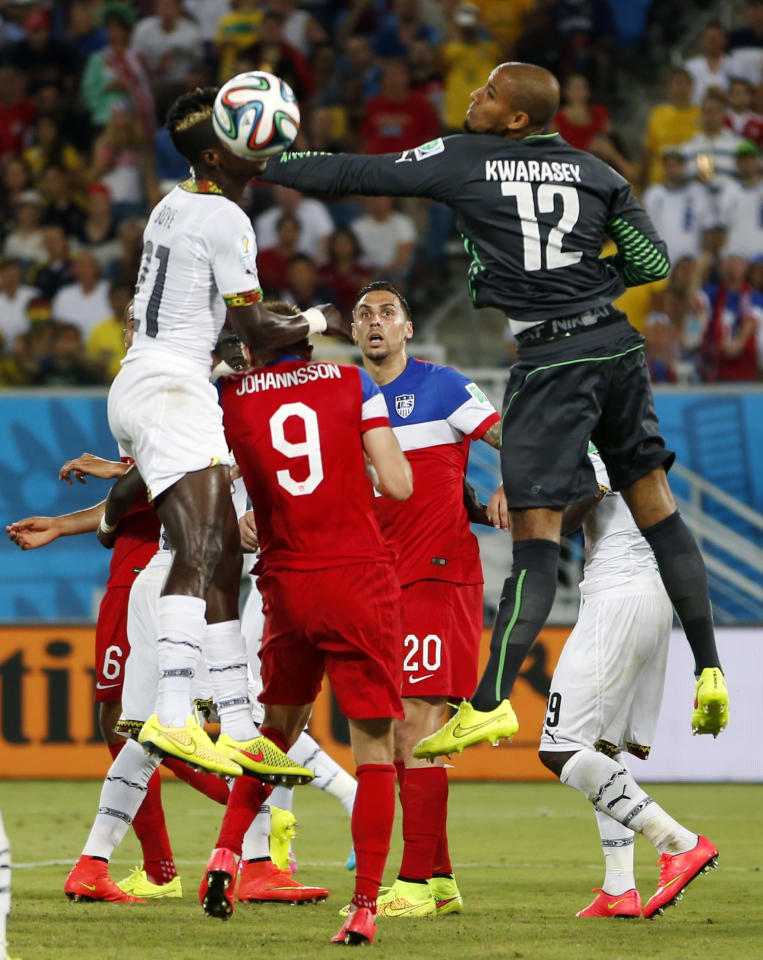 Ghana's goalkeeper Adam Kwarasey (12) leaps up to bat the ball away from United States' Aron Johannsson (9) and Geoff Cameron (20) during the group G World Cup soccer match between Ghana and the United States at the Arena das Dunas in Natal, Brazil, Monday, June 16, 2014. (AP Photo/Julio Cortez)