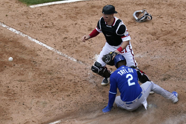 Kansas City Royals' Michael A. Taylor (2) scores on a throwing error by Chicago White Sox relief pitcher Garrett Crochet as catcher Zack Collins, top, watches the ball during the 10th inning of a baseball game in Chicago, Sunday, April 11, 2021. (AP Photo/Nam Y. Huh)