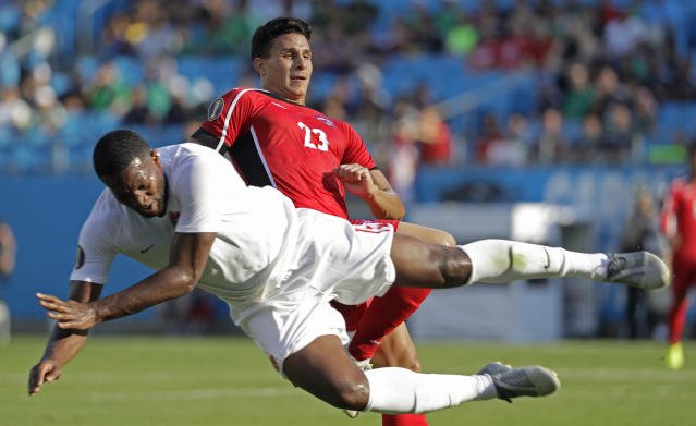 Canada's Doneil Henry, left, dives past Cuba's Luis Paradela (23) during the first half of their CONCACAF Golf Cup soccer match in Charlotte, N.C., Sunday, June 23, 2019. (AP Photo/Chuck Burton)