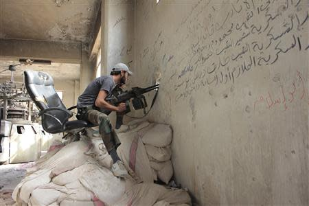 A Free Syrian Army fighter sits at a shooting position in the al-Khalidiya neighbourhood of Aleppo, September 21, 2013. REUTERS/Aref Hretani