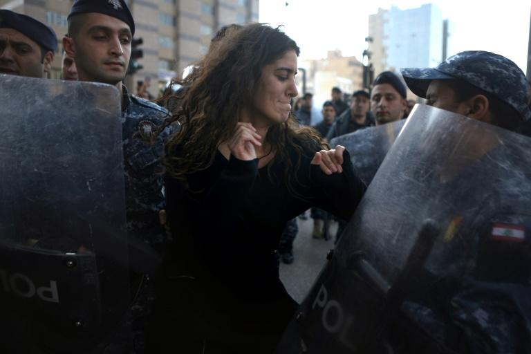 A Lebanese anti-corruption protester is surrounded by riot police during a demonstration in downtown Beirut