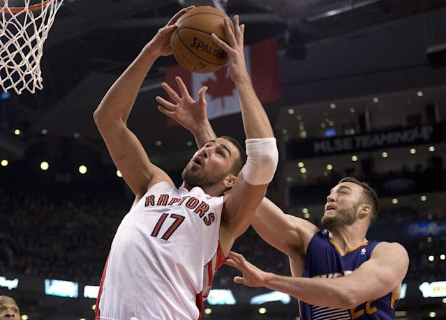 Toronto Raptors center Jonas Valanciunas (17) rebounds against Phoenix Suns center Miles Plumlee (22) during first-half NBA basketball game action in Toronto, Sunday March 16, 2014. (AP Photo/The Canadian Press, Frank Gunn)