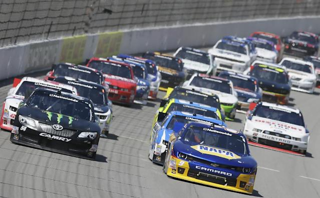 Drivers Chase Elliott, front right, and Kyle Busch, front left, lead the pack through the first turn during the NASCAR Nationwide series auto race at Michigan International Speedway in Brooklyn, Mich., Saturday, June 14, 2014. (AP Photo/Carlos Osorio)