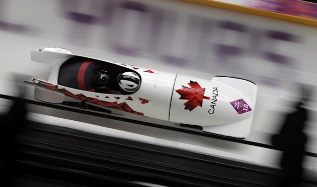 The team from Canada CAN-3, piloted by Justin Kripps and brakeman Bryan Barnett, take a turn during the men's two-man bobsled competition at the 2014 Winter Olympics, Monday, Feb. 17, 2014, in Krasnaya Polyana, Russia. (AP Photo/Michael Sohn)