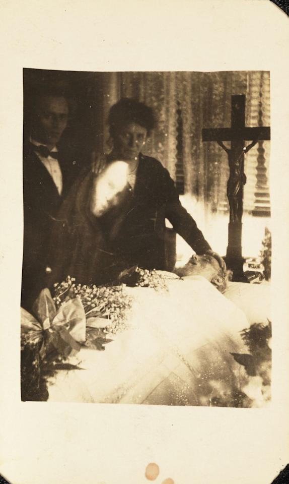 <p>As a woman mourns her deceased husband, his superimposed face looks over his lifeless body.</p>