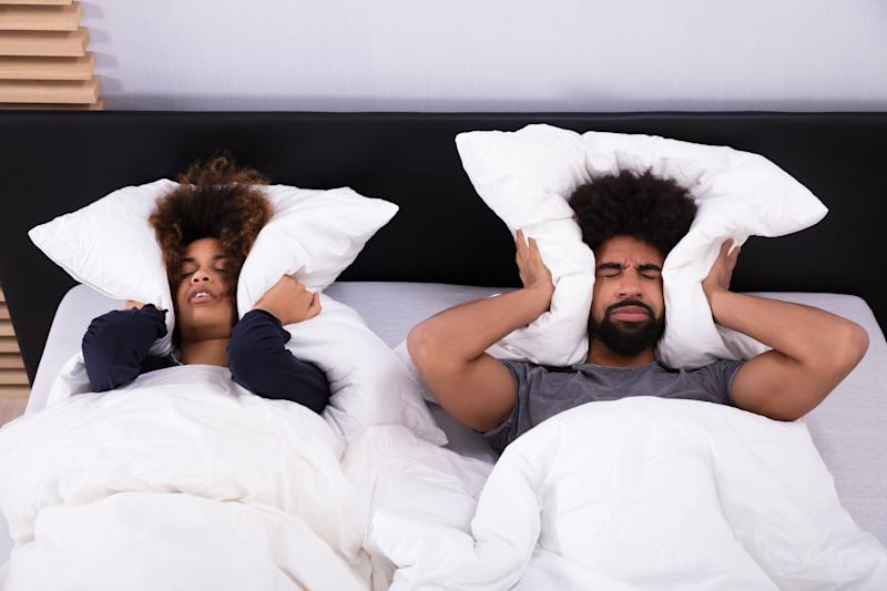 Young couple lying Inbed covering their ears with a pillow