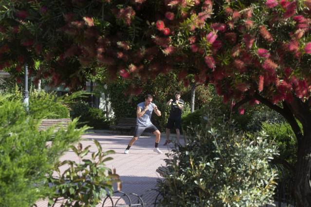 A man practices boxing in one of many parks that have now opened in Madrid, Spain, Monday, May 25, 2020. Spain is making progress on its staggered plan out of the confinement against the coronavirus. Roughly half of the population, including residents in the biggest cities of Madrid and Barcelona, enters phase 1, Monday which allows for social gatherings in limited numbers, restaurant and bar services with outdoor sitting and some cultural and sports activities. (AP Photo/Paul White)