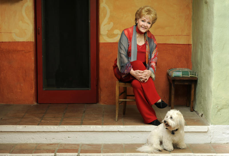 """In this Tuesday, May 21, 2013 photo, Debbie Reynolds, a cast member in the film """"Behind the Candelabra,"""" poses for a portrait with her dog, Dwight, in Beverly Hills, Calif. Reynolds plays Frances, the mother of the pianist and vocalist, Liberace. HBO debuts """"Behind the Candelabra"""" in the US, Sunday, May 26, 2013. (Photo by Chris Pizzello/Invision/AP"""