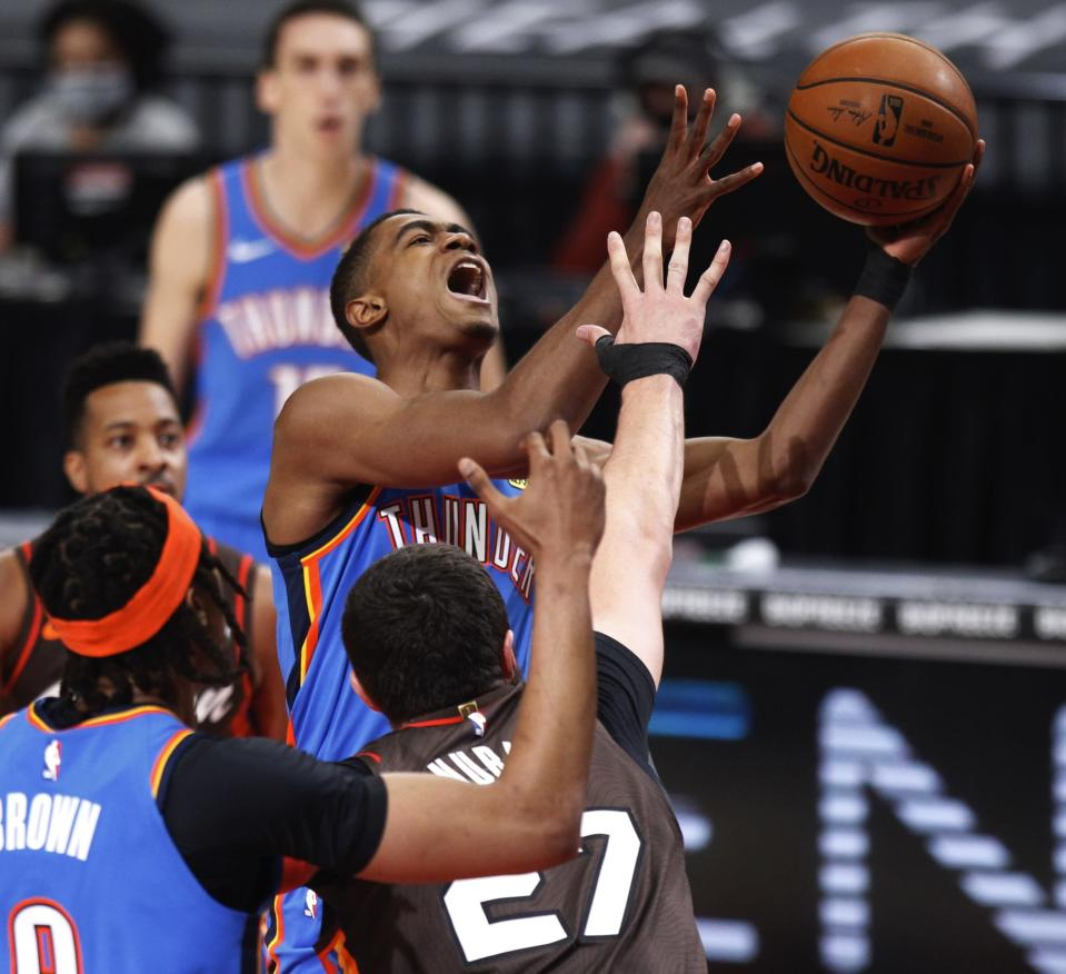 Oklahoma City Thunder guard Theo Maledon, top, shoots over the defense of Portland Trail Blazers center Jusuf Nurkic, bottom, during the first half of an NBA basketball game in Portland, Ore., Saturday, April 3, 2021. (AP Photo/Steve Dipaola)