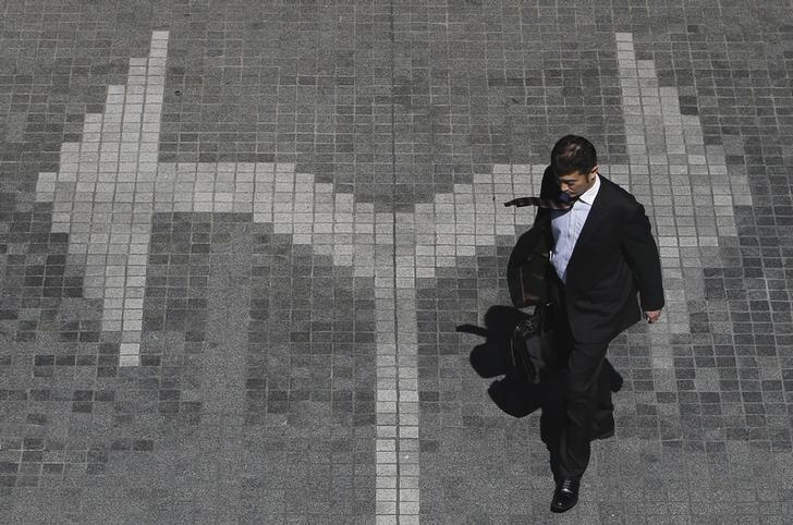A man walks on a traffic sign in the taxi stand of a building at a business district in Tokyo