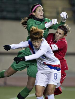 South Korea's Ga Eul Jeon (9) and Canada's Christine Sinclair (12) crash into goal keeper Stephanie Labbe (21) during the second half of an international friendly soccer match, Wednesday, Oct. 30, 2013, in Edmonton, Alberta. (AP Photo/The Canadian Press, Jason Franson)
