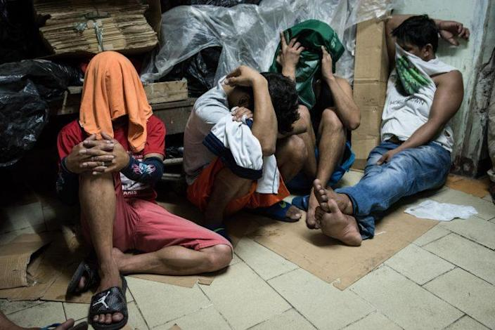 Alleged drug suspects cover their faces during a drug raid in Manila, Philippines.