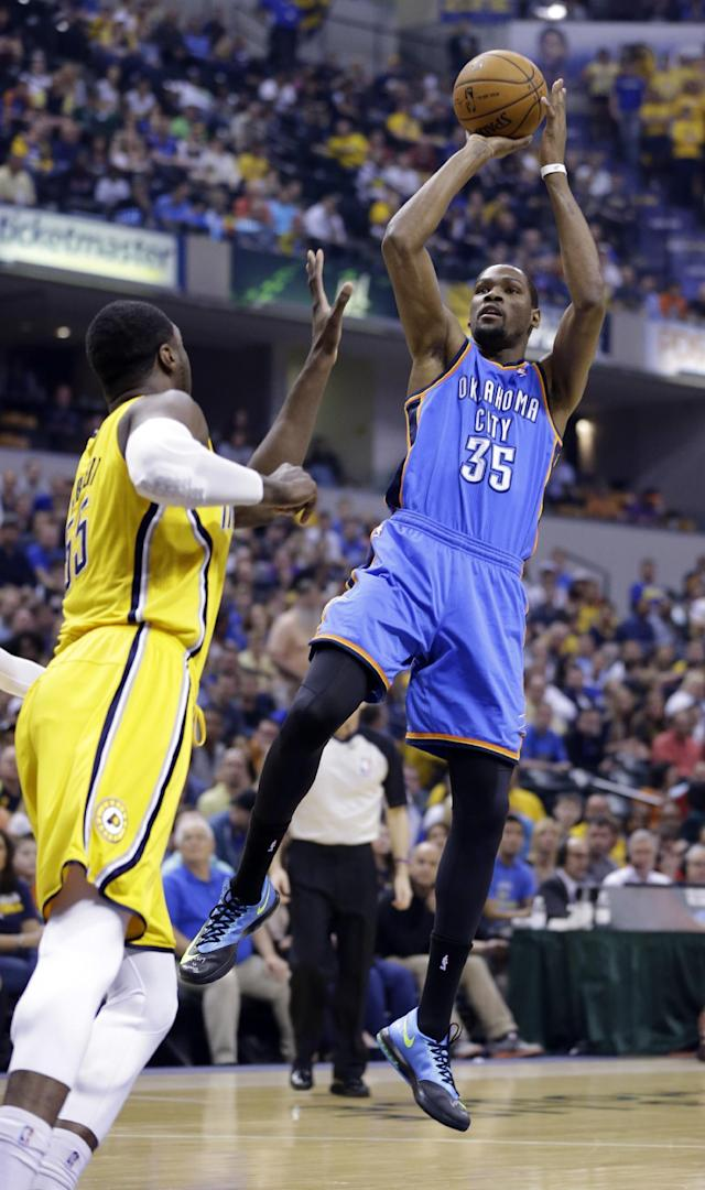 Oklahoma City Thunder forward Kevin Durant, right, shoots over Indiana Pacers center Roy Hibbert in the second half of an NBA basketball game in Indianapolis, Sunday, April 13, 2014. (AP Photo/Michael Conroy)