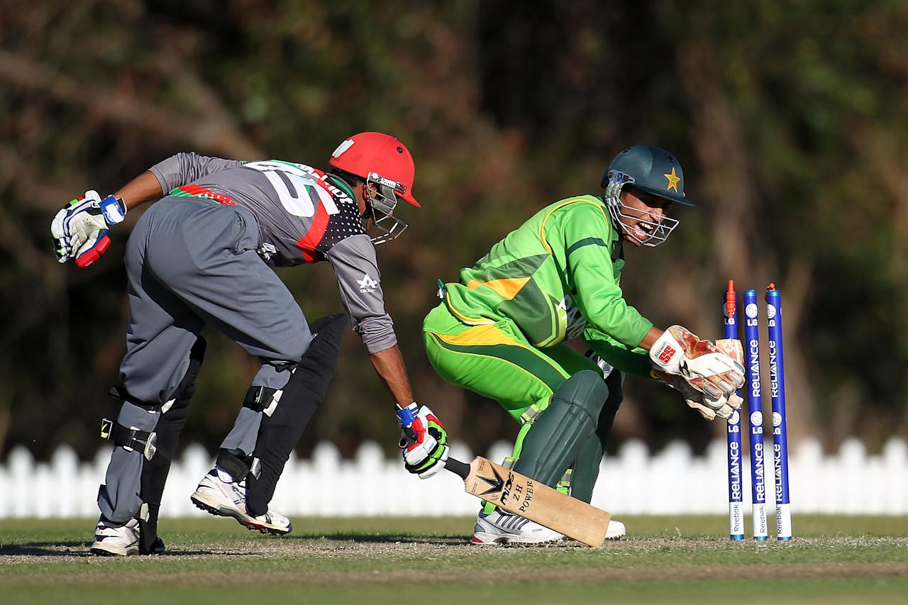 SUNSHINE COAST, AUSTRALIA - AUGUST 11:  Salman Afridi of Pakistan (R) attempts to stump the wicket as Hashmatullah Shaidi of  Afghanistan races back during the ICC U19 Cricket World Cup 2012 match between Pakistan and Afghanistan at John Blanck Oval on August 11, 2012 in Sunshine Coast, Australia.  (Photo by Graham Denholm-ICC/Getty Images)