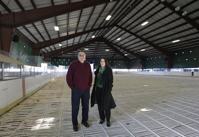"""In this photo taken on Wednesday, Nov. 13, 2013, Secaucus Mayor Michael Gonnelli, left, poses for a photographs with community outreach coordinator Lee Penna at the preparation of a skating rink in Secaucus, N.J. Northern New Jersey towns hoping to get Super Bowl visitors to spend time and money in the Garden State and not just across the river in Manhattan, realize they need to come up with a creative game plan to separate itself from New York. There's a catch: None of the festivities can employ the words """"Super Bowl,"""" a name that is trademarked by the NFL. (AP Photo/Julio Cortez)"""