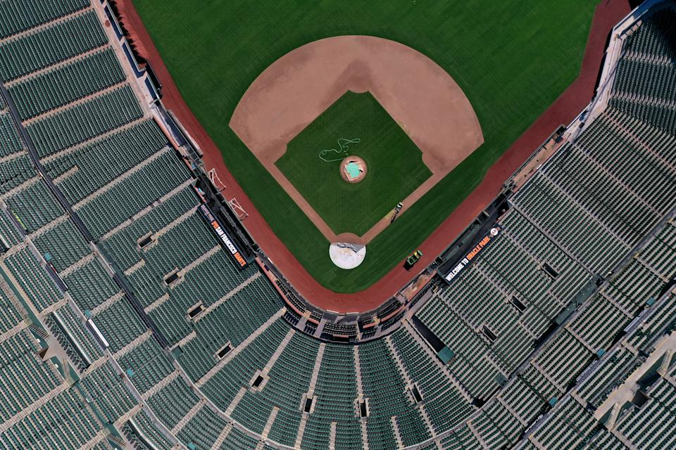 "SAN FRANCISCO, CALIFORNIA  - MARCH 26:  An aerial view from a drone shows Oracle Park, home of the San Francisco Giants, empty on Opening Day March 26, 2020 in San Francisco, California. Major League Baseball Commissioner Rob Manfred recently said the league is ""probably not gonna be able to"" play a full 162 game regular season. (Photo by Justin Sullivan/Getty Images)"