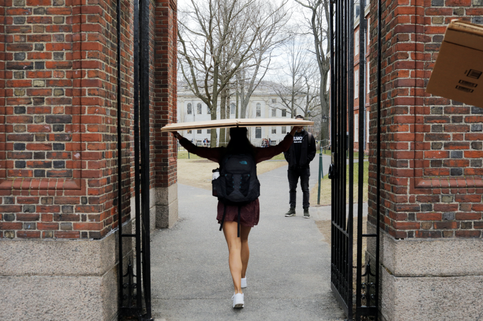 A student carries a box to her dorm at Harvard University after the school asked its students not to return to campus after Spring Break in Cambridge, Massachusetts, U.S., March 10, 2020. (Photo: REUTERS/Brian Snyder)