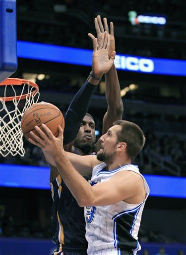 Orlando Magic's Ryan Andersongoes to the basket in front of Indiana Pacers' Roy Hibbert during the first half of an NBA basketball game Sunday, March 11, 2012, in Orlando, Fla. (AP Photo/John Raoux)