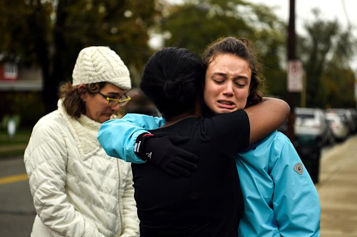 From left, Kate Rothstein looks on as Tammy Hepps hugs Simone Rothstein, 16, on the intersection of Shady Avenue and Northumberland Street after multiple people were shot at the Tree of Life Congregation synagogue. (Photo: ASSOCIATED PRESS)