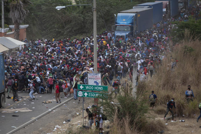 Honduran migrants, top, stand between cargo trucks as they confront Guatemalan soldiers and police blocking them from advancing toward the US, on the highway in Vado Hondo, Guatemala, Monday, Jan. 18, 2021. The roadblock was strategically placed at a chokepoint on the two-lane highway flanked by a tall mountainside and a wall leaving the migrants with few options. (AP Photo/Sandra Sebastian)