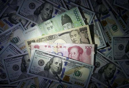 South Korean won, Chinese yuan and Japanese yen notes are seen on U.S. 100 dollar notes in this picture illustration taken in Seoul