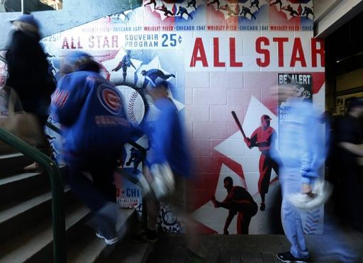 Baseball fans head to their seats past a mural of the 1947 All-Star Game program, on the 100th anniversary of the first baseball game at Wrigley Field, before a game between the Arizona Diamondbacks and Chicago Cubs, Wednesday, April 23, 2014, in Chicago. (AP Photo/Charles Rex Arbogast)