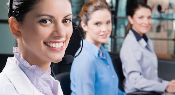 Portrait of a customer service representative smiling with her colleagues in the background