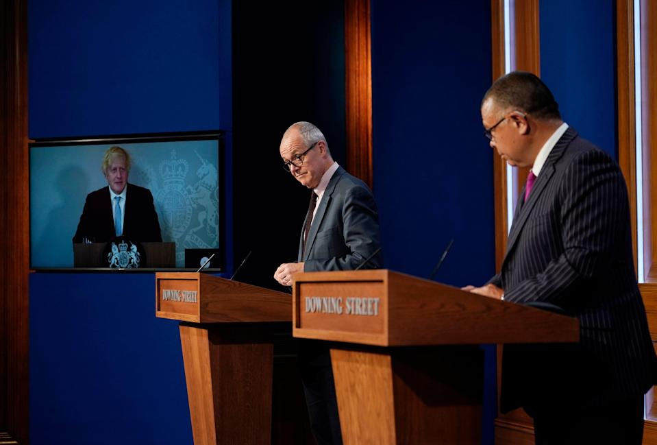 Boris Johnson on a screen from Chequers, where he is self-isolating, with Chief Scientific Advisor Patrick Vallance and Deputy Chief Medical Officer Professor Jonathan Van Tam in Downing Street during the press conference (AP)