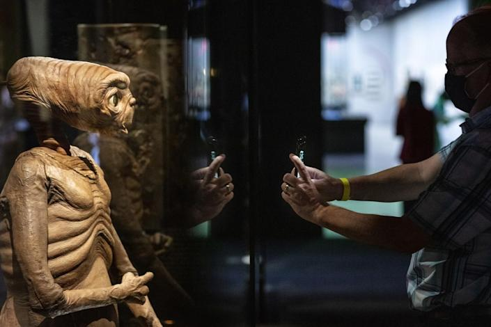 """A person holds a phone up to a glass case holding ET from """"E.T."""""""
