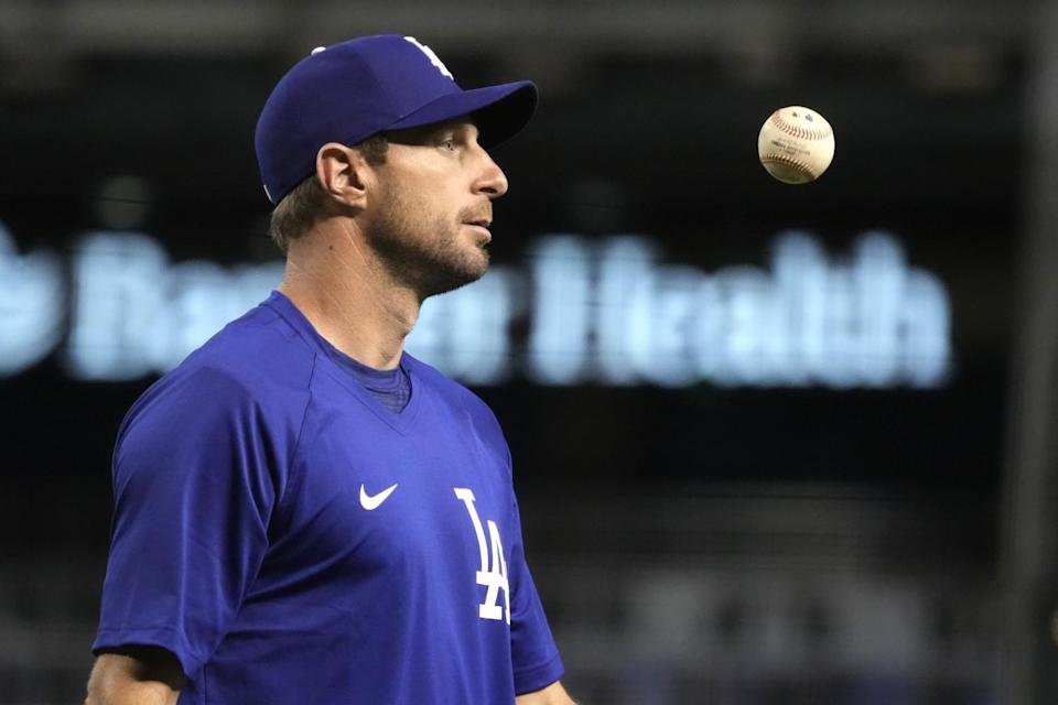 Dodgers pitcher Max Scherzer tosses a ball in the air before Sunday's game with Arizona.