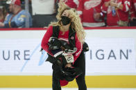 A member of the Detroit Red Wings ice crew collects hats after Tyler Bertuzzi's third goal for a hat trick against the Tampa Bay Lightning in the second period of an NHL hockey game Thursday, Oct. 14, 2021, in Detroit. (AP Photo/Paul Sancya)