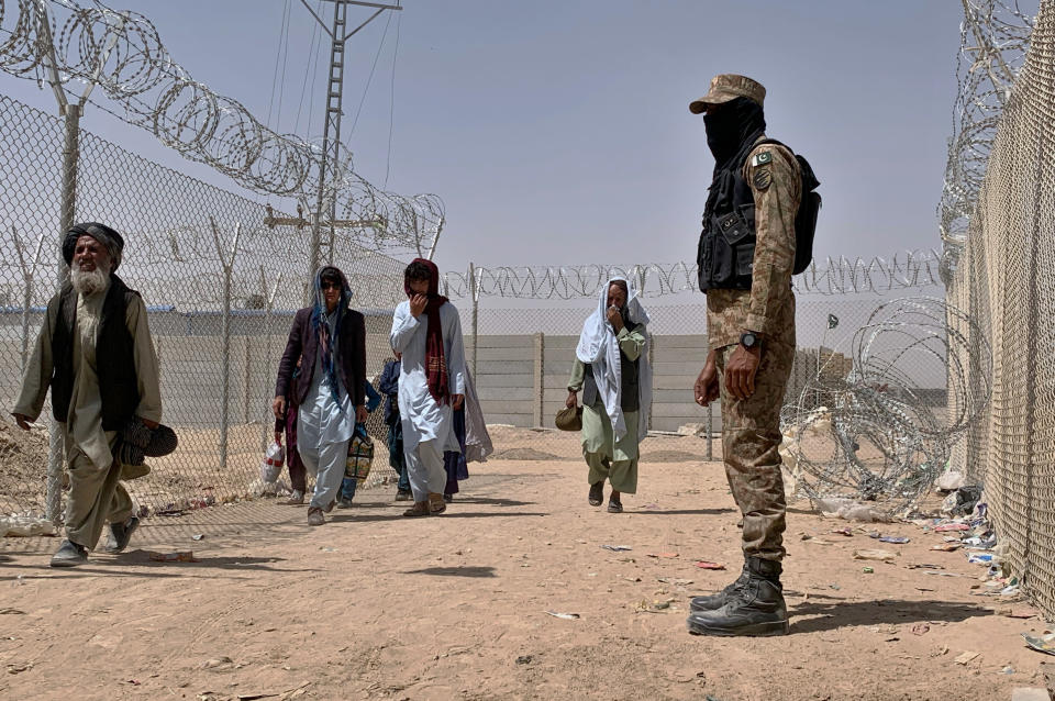 A Pakistani army soldier stands guard while Afghan people enter into Pakistan through a border crossing point, in Chaman, Pakistan, Friday, Aug. 20, 2021. Chaman is a key border crossing between Pakistan and Afghanistan, where normally thousands of Afghans and Pakistanis cross daily and a steady stream of trucks passes through, taking goods to Afghanistan. (AP Photo)