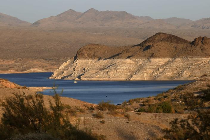 """<div class=""""inline-image__caption""""><p>Mineral-stained rocks are shown at Echo Bay on June 21, 2021 in the Lake Mead National Recreation Area, Nevada. The U.S. Bureau of Reclamation reported that Lake Mead, North America's largest artificial reservoir, dropped to just over 1,070 feet above sea level over the weekend, the lowest it's been since being filled in 1937 after the construction of the Hoover Dam.</p></div> <div class=""""inline-image__credit""""> Ethan Miller/Getty</div>"""
