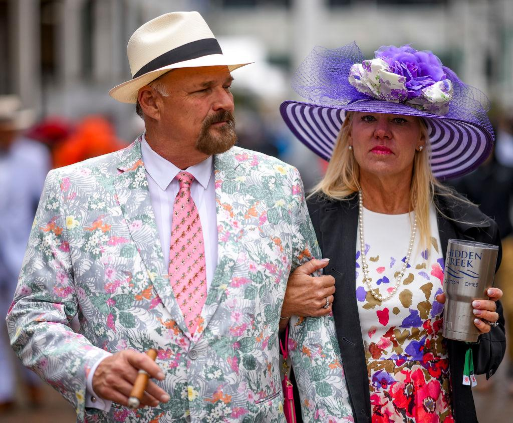 <p>A man and woman walk around Churchill Downs, perfect examples of two mainstays at the Derby: a cigar and a wide-brimmed hat. (Photo: Getty Images) </p>