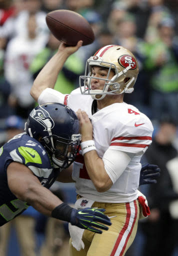 FILE - In this Dec. 2, 2018, file photo, San Francisco 49ers quarterback Nick Mullens passes under pressure from Seattle Seahawks middle linebacker Bobby Wagner during the first half of an NFL football game, in Seattle. The 49ers (2-10) host the Broncos (6-6) on Sunday. Two of the three undrafted quarterbacks to start a game in the NFL this season will square off. (AP Photo/Elaine Thompson, File)