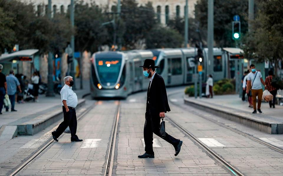 An Orthodox Jewish man, mask-clad due to the COVID-19 coronavirus pandemic, crosses a street in Jerusalem - AFP