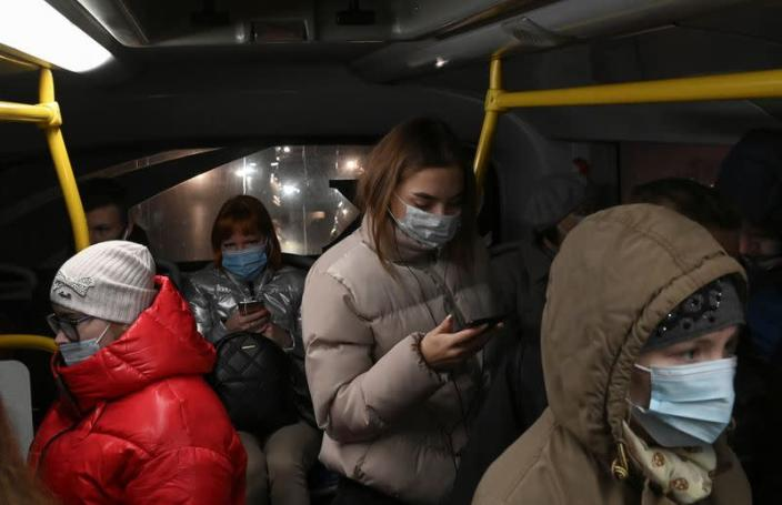 FILE PHOTO: Passengers use protective face masks inside a bus in Omsk