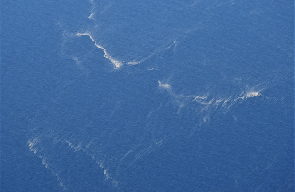In this aerial photo taken from a maritime patrol aircraft of the Indonesian 800 Air Squadron of the 2nd Air Wing of Naval Aviation Center (PUSPENERBAL), oil slicks are seen in the area where the search operation for the submarine KRI Nanggala that went missing while participating in a training exercise on Wednesday is conducted in the waters off Bali Island, Indonesia, Thursday, April 22, 2021. Indonesia's navy ships on Thursday were intensely searching for the submarine that likely fell too deep to retrieve, making survival chances for all the crew on board slim. Authorities said oxygen in the submarine would run out by early Saturday. (AP Photo/Eric Ireng)
