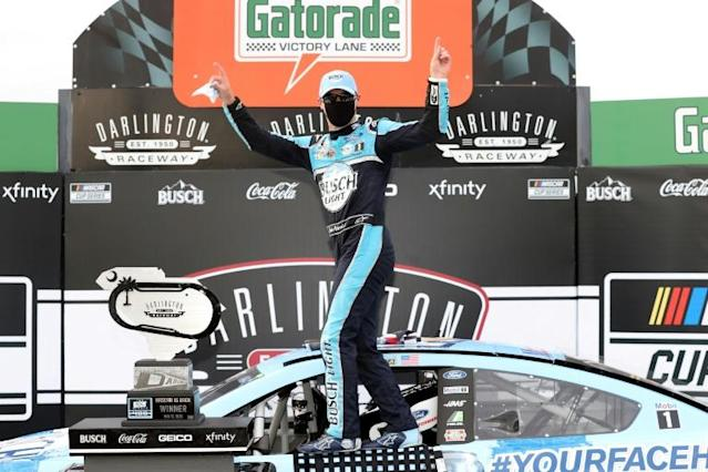 Kevin Harvick, sporting a black protective face mask, celebrates his victory after winning the NASCAR Series race at Darlington Raceway in South Carolina (AFP Photo/Chris Graythen)