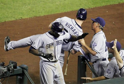 San Diego Padres' Cameron Maybin, front left, gets high-fives from teammates after hitting a home run against the Arizona Diamondbacks as manager Bud Black, top right, pulls Clayton Richard (33) closer to him so they can talk during the sixth inning of a baseball game, Monday, July 2, 2012, in Phoenix. (AP Photo/Ross D. Franklin)