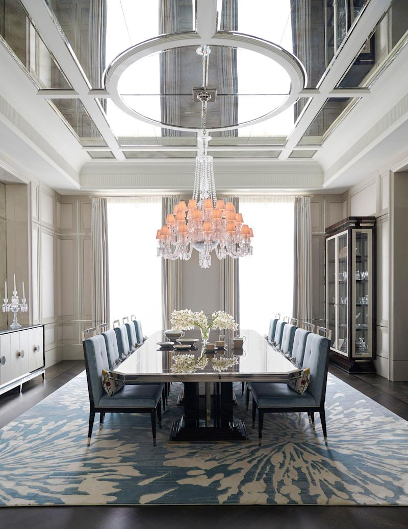 In the dining room, a 12-person table is surrounded by velvet chairs, all by Rafauli. Baccarat chandelier.