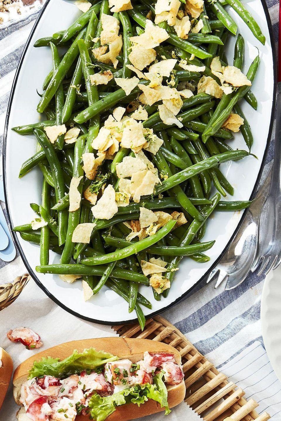 """<p>Blanched green beans get topped with a crumbled chip, parsley, and lemon zest topping.<br></p><p><strong><a href=""""https://www.countryliving.com/food-drinks/a27547118/green-beans-and-crushed-salt-and-vinegar-chips-recipe/"""" rel=""""nofollow noopener"""" target=""""_blank"""" data-ylk=""""slk:Get the recipe"""" class=""""link rapid-noclick-resp"""">Get the recipe</a>.</strong></p>"""