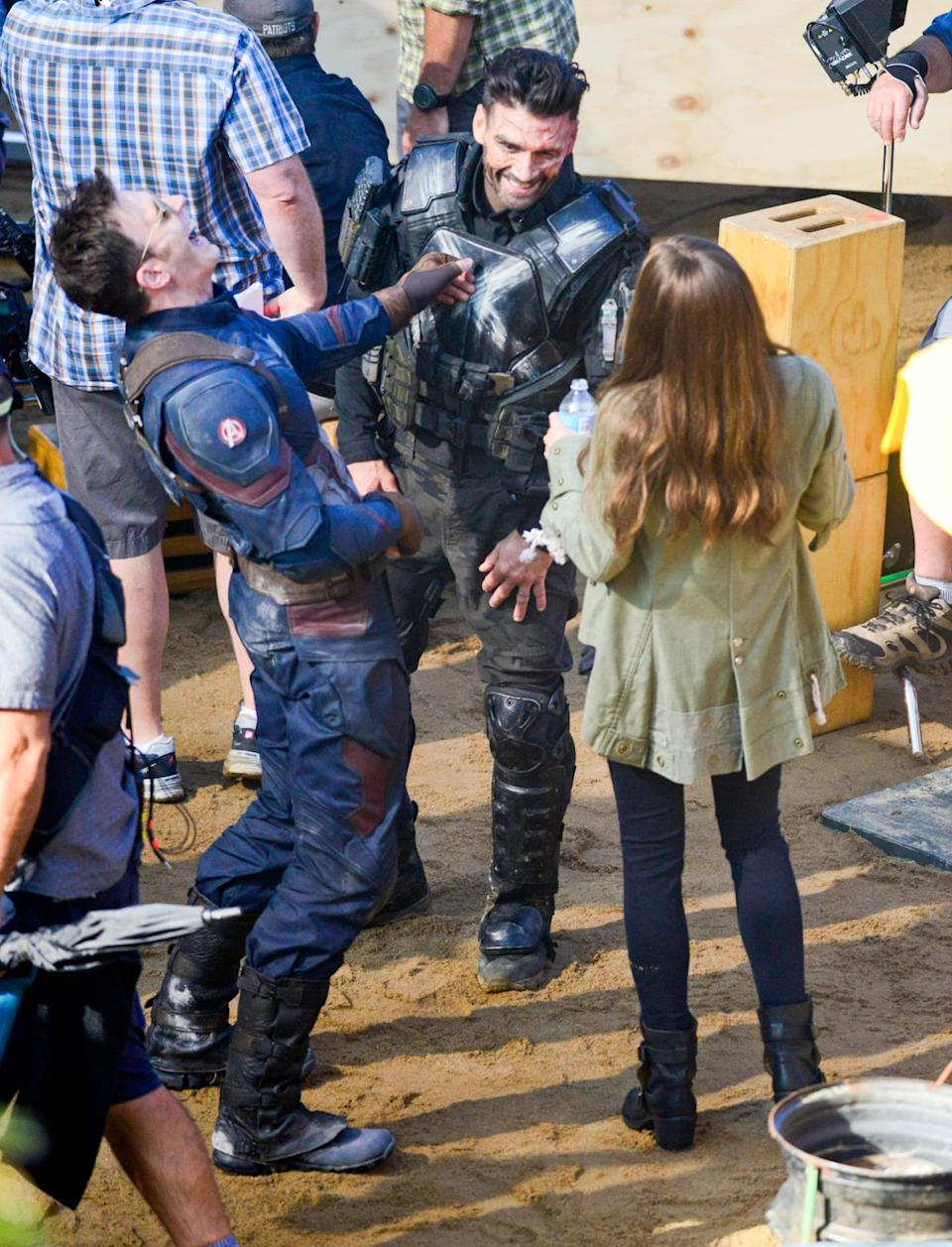 Avengers teammates Captain America (Chris Evans) and Scarlet Witch (Elizabeth Olsen) share a laugh with their mortal enemy Crossbones (Frank Grillo) in between takes on set.