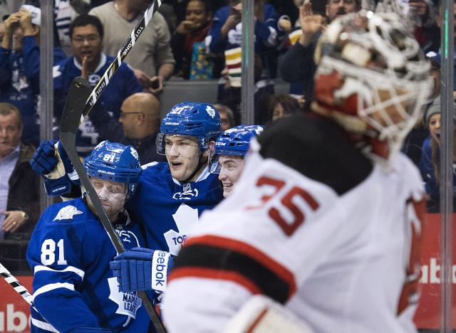 Toronto Maple Leafs forward James van Riemsdyk, center, celebrates his goal with teammate Phil Kessel, left, and Tyler Bozak, second right, as New Jersey Devils goalie Cory Schneider (35) looks on during second period NHL hockey action in Toronto on Sunday, Jan. 12, 2014. (AP Photo/The Canadian Press, Nathan Denette)
