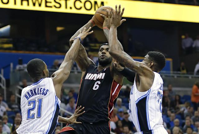Miami Heat's LeBron James (6) makes a shot as he is guarded by Orlando Magic's Maurice Harkless (21) and Solomon Jones, right, during the first half of an NBA basketball game in Orlando, Fla., Wednesday, Nov. 20, 2013. (AP Photo/John Raoux)